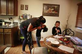 Latifa Lewis (left) gets a hug from her daughter Taylor Lewis (center), 4, after arriving back at home after looking at an apartment for rent as Kamil Lewis (right), 5, works on her writing at the dinning table on Wednesday, January 23, 2013 in Hayward, Calif.