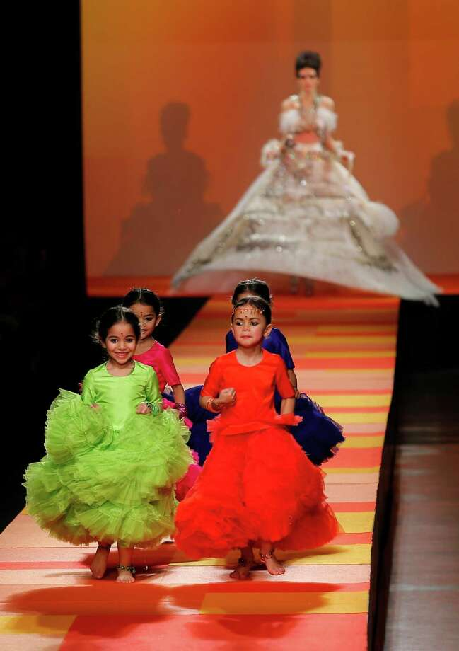 Children run ahead of a model wearing a wedding gown for French fashion designer Jean-Paul Gaultier. Photo: AP