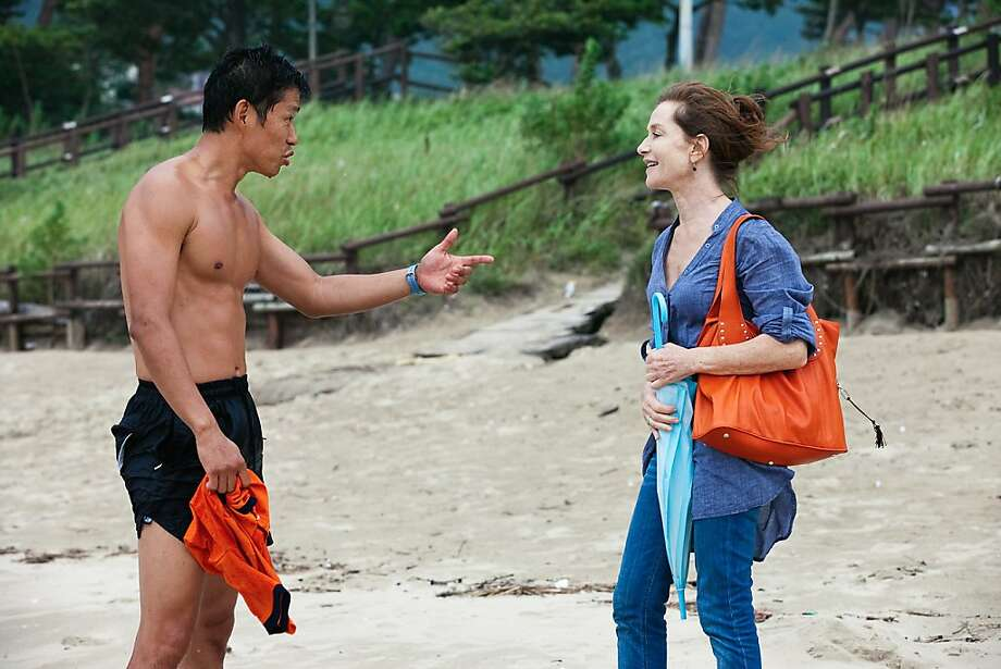 "Yu Jun-sang plays a local lifeguard who wants Anne (Isabelle Huppert) to visit his tent on the beach in one of three vignettes that make up ""In Another Country,"" by South Korea's Hong Sang-soo. Photo: Kino Lorber, Inc."