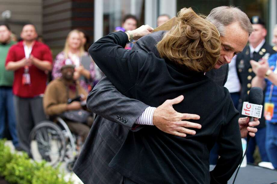 Terry Marks, CEO of Hooters of America, embraces Rosie Babin, director of Help Our Wounded, after Marks presents her with a $35,000 check for the organization that helps injured veterans.  Photo: Brett Coomer, Houston Chronicle / © 2013 Houston Chronicle