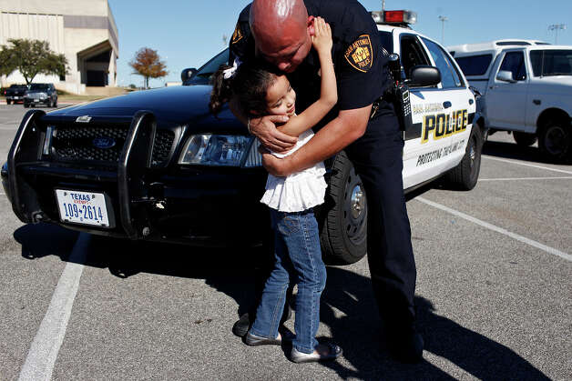 SAPD officer Joe Uribe hugs his daughter, one of his three children. Uribe's wife, Allison Uribe, is the founder of Wives on Duty. Photo: Lisa Krantz, San Antonio Express-News / © 2012 San Antonio Express-News