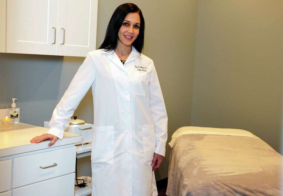 Debra Sullivan, a certified Physician Assistant specializing in Aesthetics and owner of Newtown Medi Spa, stands in one of the massage rooms at the new spa at 123 South Main St. in Newtown, Conn. Photo: Autumn Driscoll / Connecticut Post
