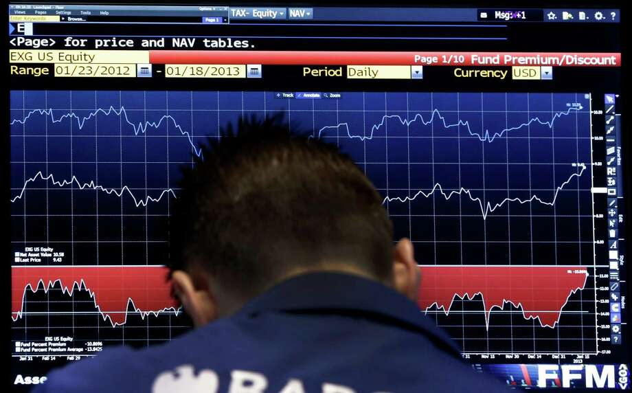 A specialist checks a screen as his post on the floor of the New York Stock Exchange Tuesday, Jan. 22, 2013. World stock markets fell Wednesday Jan. 23, 2013 ahead of a U.S. vote on raising the nation's borrowing limit.  (AP Photo/Richard Drew) Photo: Richard Drew