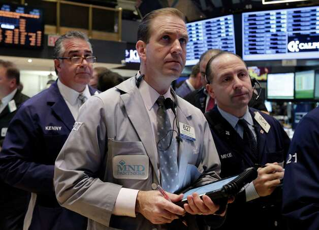 Trader Michael Smyth, center, works on the floor of the New York Stock Exchange Wednesday, Jan. 23, 2013. Stocks are opening mostly higher on Wall Street following strong earnings reports from Google, IBM and railroad operator CSX. (AP Photo/Richard Drew) Photo: Richard Drew / AP