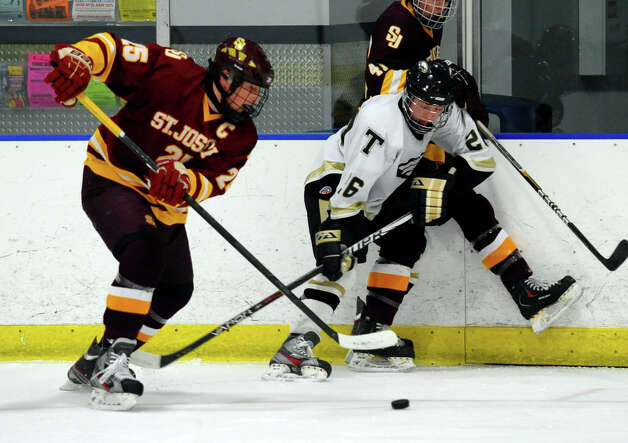 St. Joseph's #25 Andrew Gore, left, and Trumbull's #26 Nick Cirino scramble for the puck, during hockey action in Shelton, Conn. on Wednesday January 23, 2013. Photo: Christian Abraham / Connecticut Post