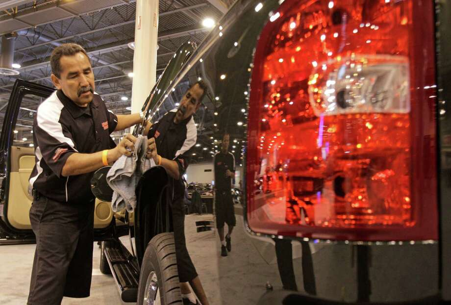 Smiley Castaneda of Lake Forest, CA with Professional Detailers works on a Chevrolet Silverado truck Tuesday, Jan. 22, 2013, in Houston as crews prepare for the opening of the Houston Auto Show in Reliant Center, Tuesday, Jan. 22, 2013, in Houston.   The show runs from Jan. 23 through Jan. 27. Photo: Melissa Phillip, Houston Chronicle / © 2013 Houston Chronicle