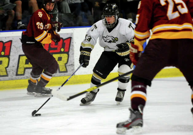 Trumbull's #13 Brendan McGill weaves his way between two St. Joseph players, during hockey action in Shelton, Conn. on Wednesday January 23, 2013. Photo: Christian Abraham / Connecticut Post