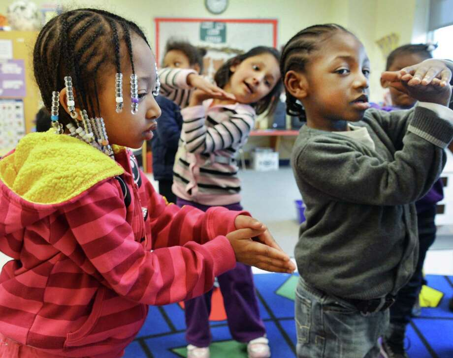 Pre-kindergarten students , from left, Bri'aja nae Walker, Nisha Biswa and Nyier Mott sinf and dance during class at Sheridan Preparatory Academy in Albany Tuesday Jan. 22, 2013.  (John Carl D'Annibale / Times Union) Photo: John Carl D'Annibale / 00020870A