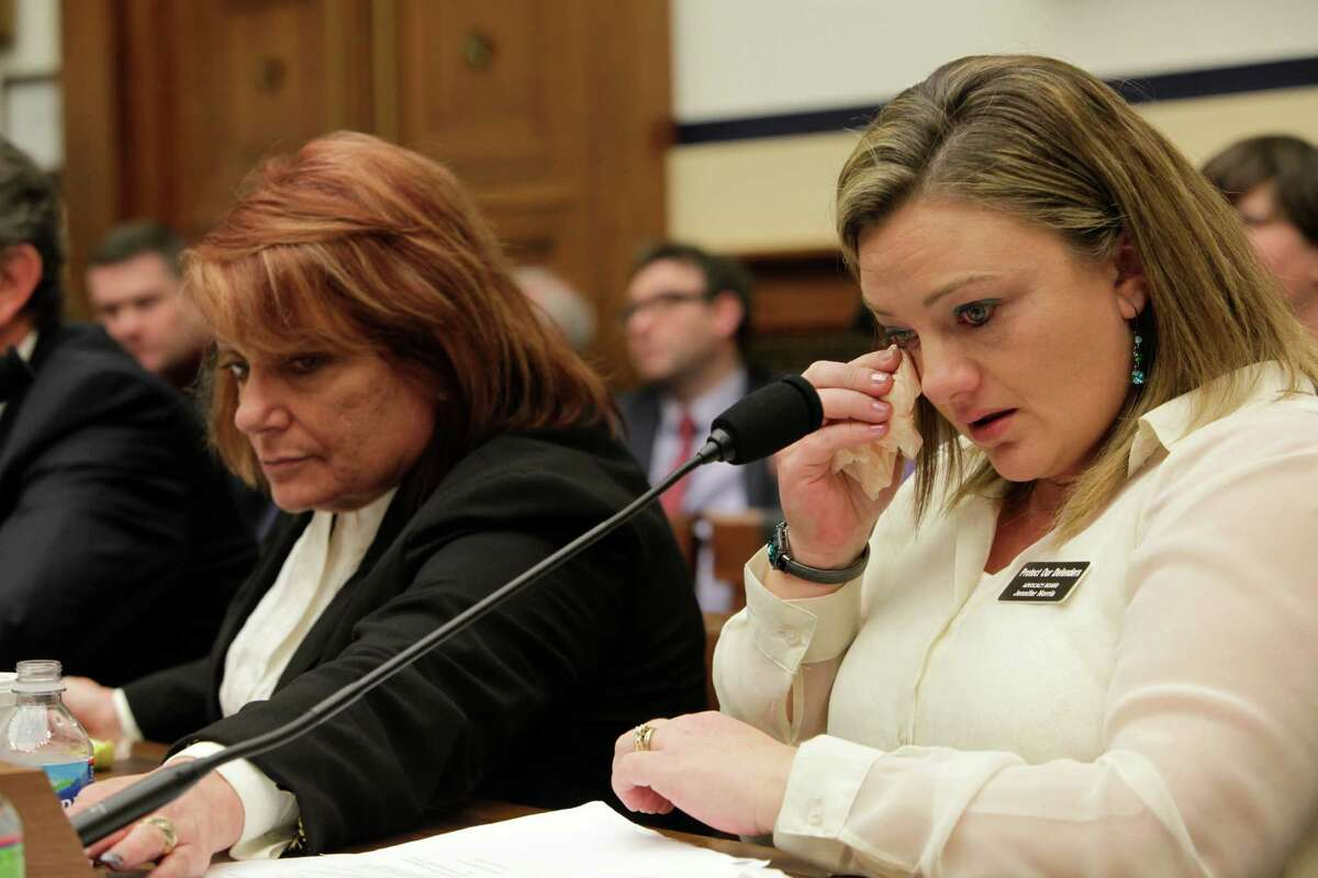WASHINGTON, DC - January 23 - Technical Sergeant Jennifer Norris, USAF, (ret) wipes a tear as she testifies at a review of sexual misconduct by basic training instructors at Lackland Air Force Base by House Armed Services Committee, 2118 Rayburn Building. At left is witness Chief Master Sergeant Cindy McNally, USAF(ret) reaching to turn off Norris's microphone.
