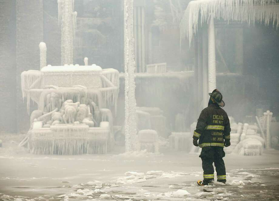 Firefighters help to extinguish a massive blaze at a vacant warehouse on January 23, 2013 in Chicago, Illinois. More than 200 firefighters battled a five-alarm fire as temperatures were in the single digits. Photo: Scott Olson, Getty Images / 2013 Getty Images