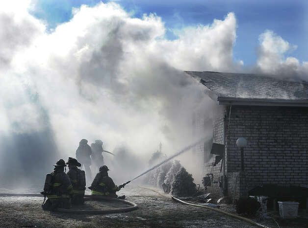 Fire fighters from five fire departments battle a house fire in freezing weather, Tuesday morning, Jan. 22, 2013 at 10110 39th Ave. in Pleasant Praire, Wis. According to the Kenosha News, two people were taken to the hospital. The fire started in the basement. The cause remains undetermined but it appears to have been electrical. Photo: Bill Siel, Associated Press / KENOSHA NEWS