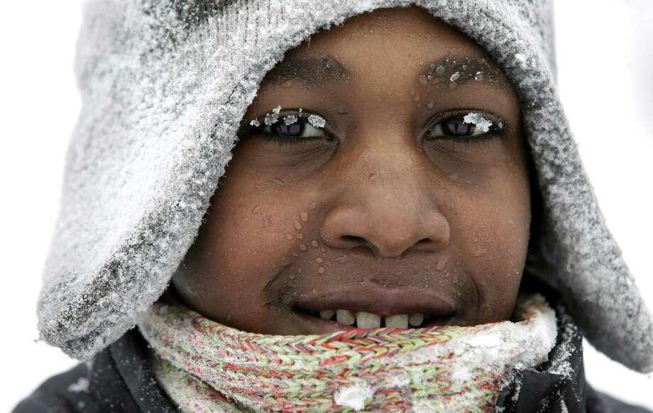 Ice crystals cling to 11-year-old Deimetrius Lamier's eyelashes while he spends his snow day sledding at Maple Street Magnet School Tuesday, Jan. 22, 2013, in Kalamazoo, Mich. Photo: Mark Bugnaski, Associated Press / The Kalamazoo Gazette