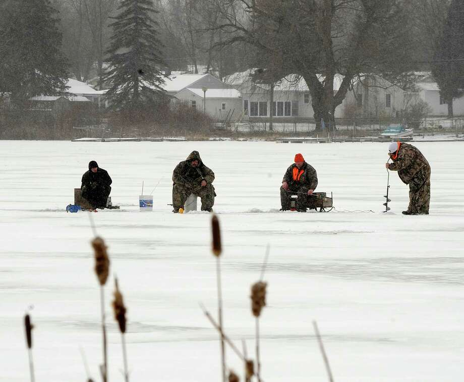 On one of the coldest days of the year, ice fishermen brave the cold on Bush Lake in Holly, Mich., Wednesday Jan. 23, 2013.  A bitter cold snap continues to grip Michigan, forcing school closures and prompting warming centers to extend hours for those most at risk. Photo: Charles V. Tines, Associated Press / The Detroit News