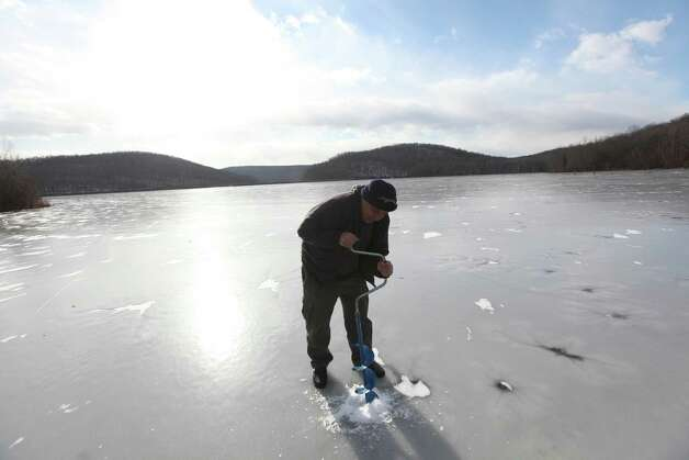 Joe Krysztofik of Garfield drills a hole to test the thickness of the ice covering Monksville Reservoir in West Milford, N.J., Wednesday, Jan. 23, 2013. He plans on coming back tomorrow to go ice fishing. Photo: Chris Pedota, Associated Press / The Record of Bergen County