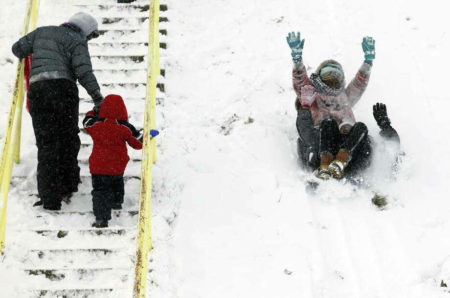People spend a snow day sledding at Maple Street Magnet School Tuesday, Jan. 22, 2013, in Kalamazoo, Mich. Photo: Mark Bugnaski, Associated Press / The Kalamazoo Gazette