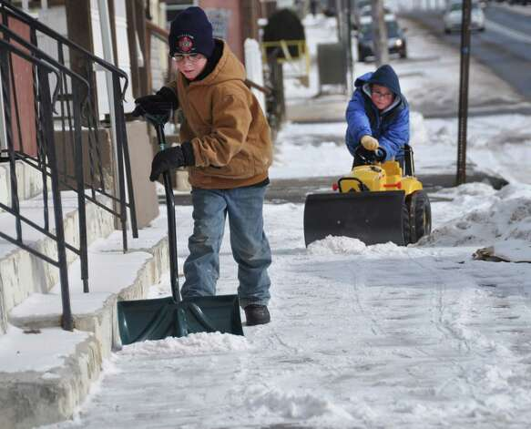 Despite single digit temperatures, Jordan Klein, 10, uses a shovel to clear the snow from the sidewalk near his grandmother's home in Hazleton, Pa., Tuesday Jan. 22, 2013 as his eight-year-old brother Jayden works in tandem by pushing his toy tractor.   The two boys took advantage of a day off of school on Tuesday and spent some time outdoors. Photo: Ellen F. O'Connell, Associated Press / HAZLETON STANDARD-SPEAEKER