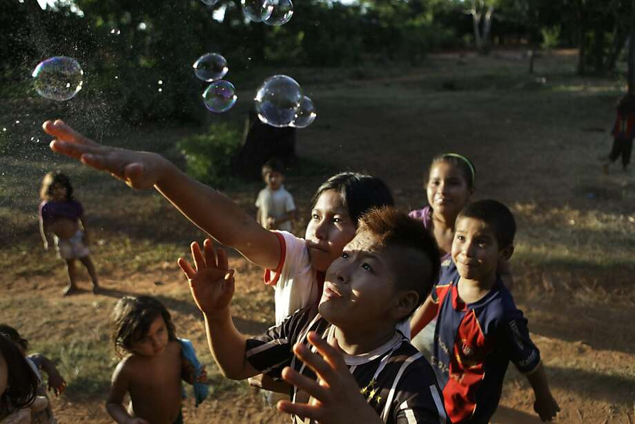 In this Jan. 20, 2013 photo, children play with bubbles during events celebrating the 12th anniversary of the village of Kuetuvy in the Canindeyu department of Paraguay. The Ache are hunter-gatherers whose population of roughly 1,200 is distributed in five villages in eastern Paraguay. They also celebrated the recent success of their exports to the United States of shade-grown, organic yerba mate, a drink brewed from the leaves of the rainforest holly tree. In 2010, Paraguay's Congress gave them formal title to the land. Photo: Jorge Saenz, Associated Press