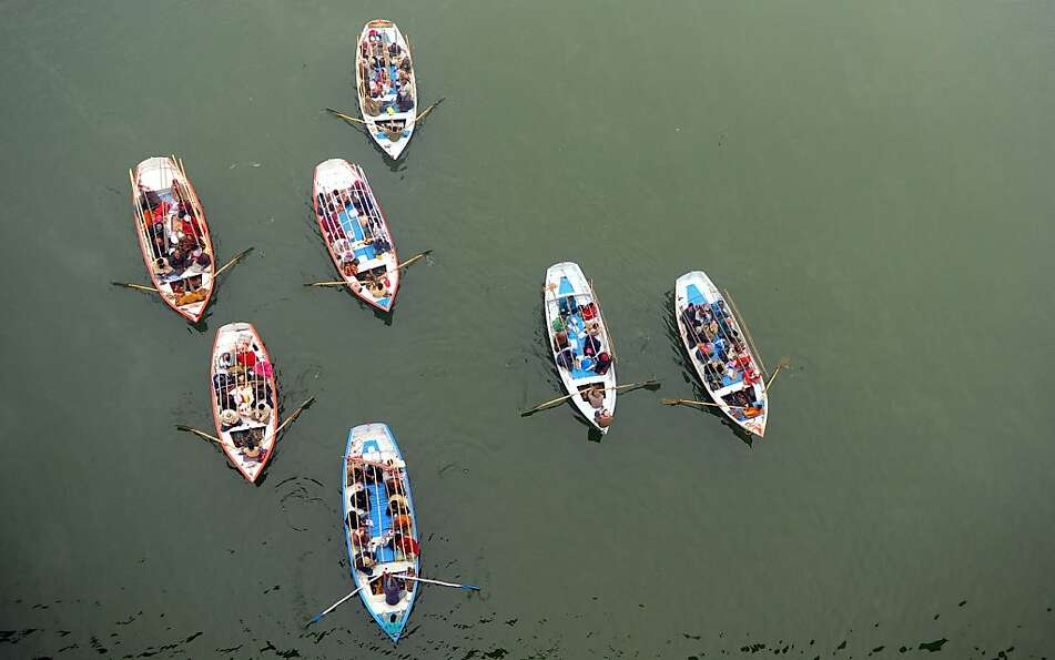 Indian Hindu pilgrims travel on boats to take a holy dip at Sangam, the confluence of the Rivers Gan