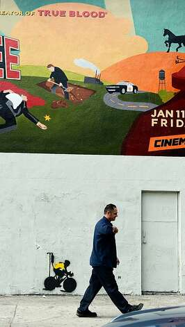 A man walks past a stencil graffiti depicting cyclist Lance Armstrong in a yellow jersey, the traditional garb of the seven-time Tour De France winner, attached to an IV drip on January 23, 2013 in Los Angeles, California. Armstrong recently admitted to using performance enhancing drugs after being found guilty by the United States Anti-Doping Agency and stripped of his titles. Photo: Kevork Djansezian, Getty Images