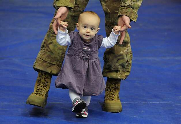 Eight-month-old Sophia Parker gets some help walking with her father Sgt. Jesse Parker after a farewell ceremony, Wednesday, Jan. 23, 2013, at the Buckner Physical Fitness Center on Joint Base Elmendorf-Richardson in Anchorage, Alaska.  Sgt. Parker will be deploying for the first time. Photo: Bill Roth, Associated Press