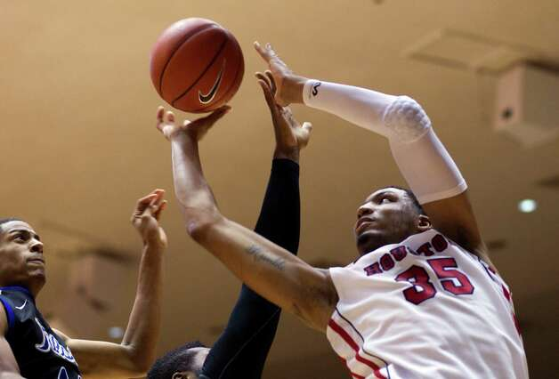 The University of Houston's TaShawn Thomas (35) puts up a shot over Tulsa's Brandon Swannegan, left, in the first half as the University of Houston played the University of Tulsa at Hofheinz Pavilion Wednesday, Jan. 23, 2013, in Houston. Photo: Johnny Hanson, Houston Chronicle / © 2013  Houston Chronicle