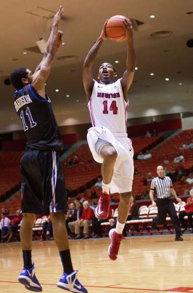 The University of Houston's Tione Womack puts up a shot over Tulsa's Shaquille Harrison in the first