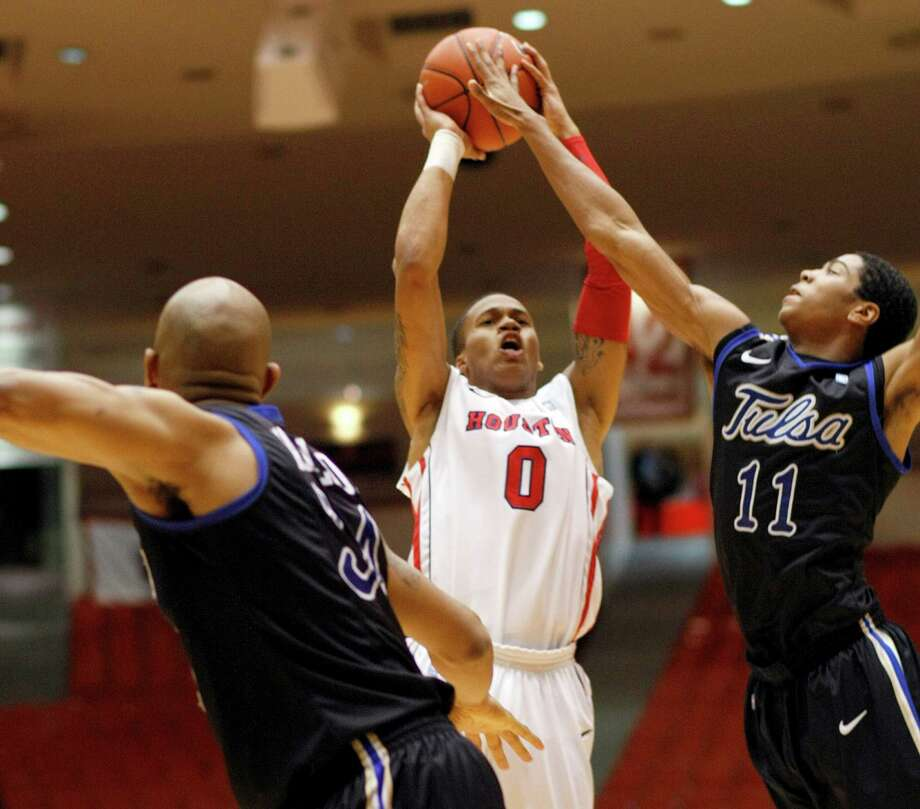 The University of Houston's Joseph Young (0) attempts to put a shot over Tulsa's Shaquille Harrison (11) in the first half as the University of Houston played the University of Tulsa at Hofheinz Pavilion Wednesday, Jan. 23, 2013, in Houston. Photo: Johnny Hanson, Houston Chronicle / © 2013  Houston Chronicle