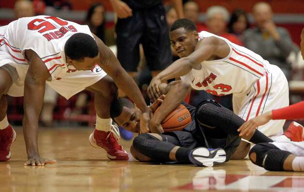 The University of Houston's Leon Gibson (15) and Danuel House (23) battle for the ball against Tulsa's Tim Peete in the first half as the University of Houston played the University of Tulsa at Hofheinz Pavilion Wednesday, Jan. 23, 2013, in Houston. Photo: Johnny Hanson, Houston Chronicle / © 2013  Houston Chronicle