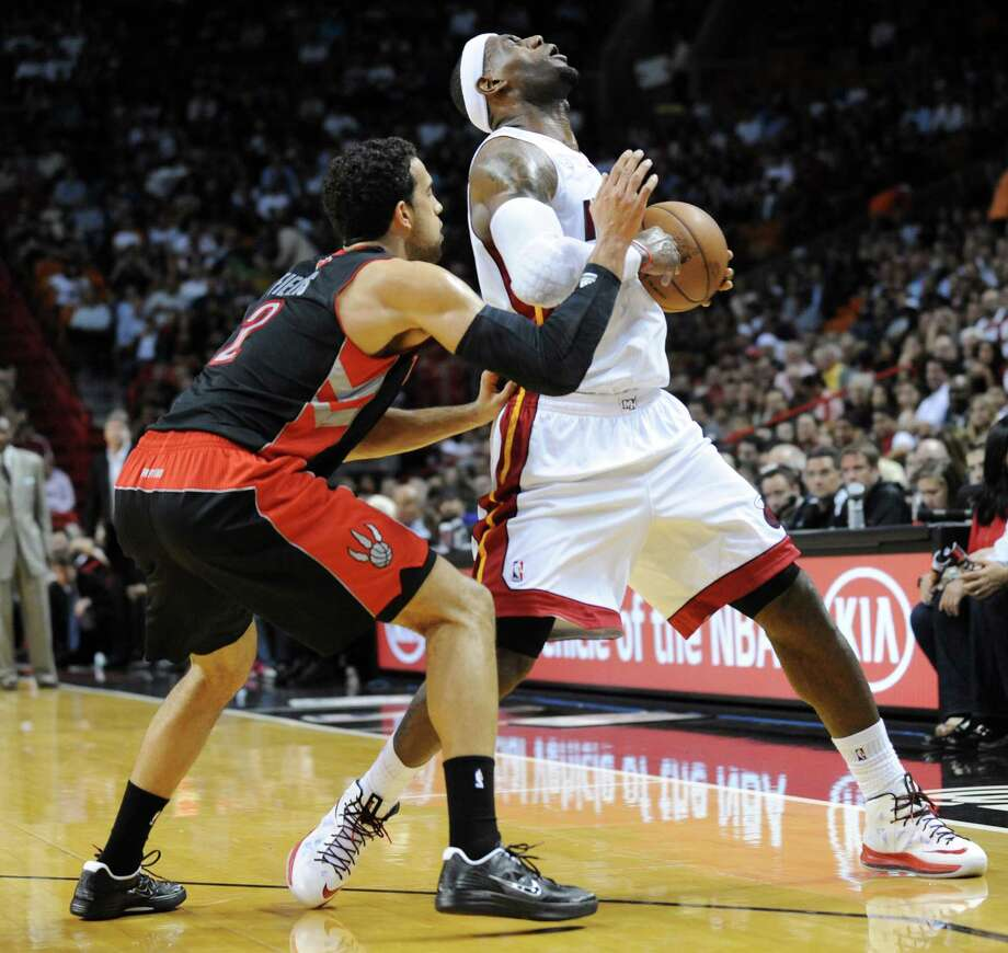 About the only thing that slowed down LeBron James on Wednesday was being hit by Landry Fields, left. Photo: Jim Rassol, MBR / Sun Sentinel