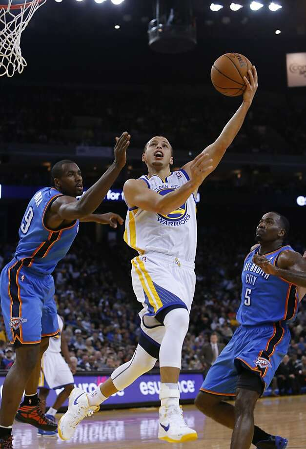 Stephen Curry puts up a shot past Serge Ibaka, left, and Kendrick Perkins, right, in the first half. The Golden State Warriors played the Oklahoma City Thunder at Oracle Arena in Oakland, Calif., on Wednesday, January 23, 2013. Photo: Carlos Avila Gonzalez, The Chronicle