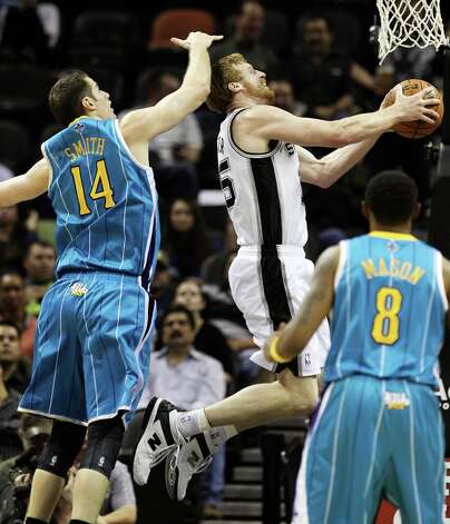 Spurs' Matt Bonner (15) attempts a layup against New Orleans Hornets' Jason Smith (14) in the first half on Wednesday, Jan. 23, 2013. Photo: Kin Man Hui, San Antonio Express-News / © 2012 San Antonio Express-News