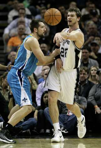 Spurs' Tiago Splitter (22) makes a pass against New Orleans Hornets' Ryan Anderson (33) in the first half on Wednesday, Jan. 23, 2013. Photo: Kin Man Hui, San Antonio Express-News / © 2012 San Antonio Express-News
