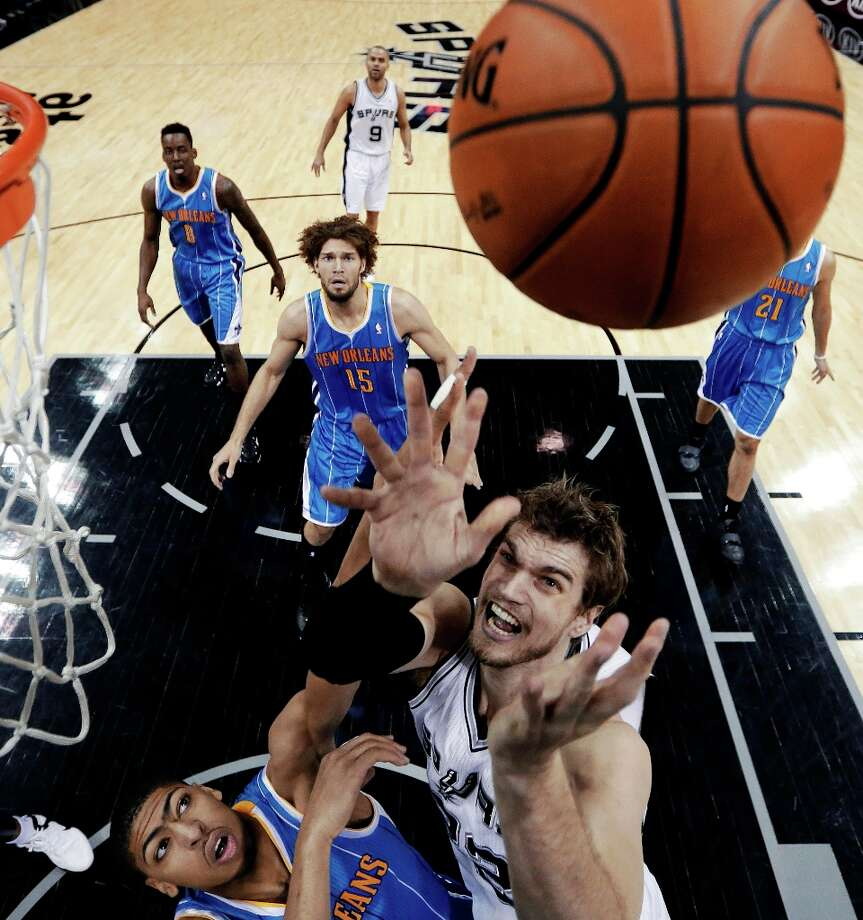 New Orleans Hornets' Anthony Davis, left, and San Antonio Spurs' Tiago Splitter, right, of Brazil, reach for a rebound during the first quarter of an NBA basketball game, Wednesday, Jan. 23, 2013, in San Antonio. Photo: Eric Gay, Associated Press / AP