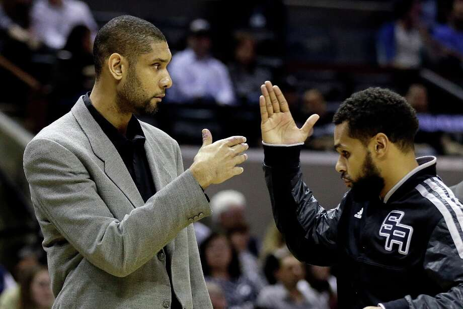 San Antonio Spurs' Tim Duncan, left, out with a sore left knee, slaps hands with teammate Patty Mills, right, during the first quarter of an NBA basketball game against the New Orleans Hornets, Wednesday, Jan. 23, 2013, in San Antonio. Photo: Eric Gay, Associated Press / AP