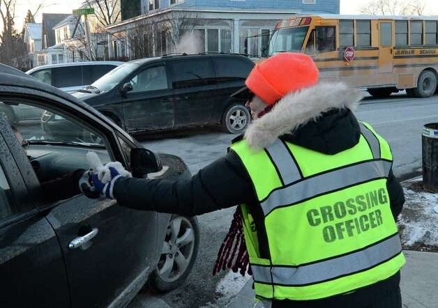 School Crossing Officer Carla Rossi receives a pair of gloves from a student she lent them to during the cold weather yesterday at her post at the intersection of Elbel St. and Whitehall Road Jan. 23, 2013 in Albany, N.Y.  Rossi has been a Crossing Officer for 14 years.  (Skip Dickstein/Times Union) Photo: SKIP DICKSTEIN