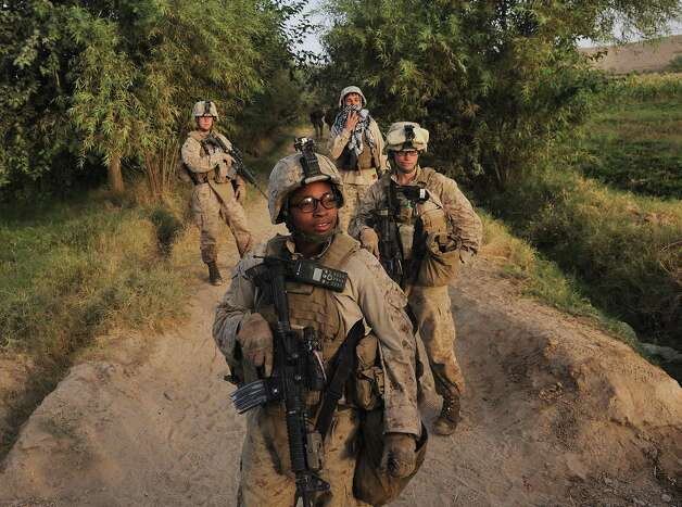 FILE -- Cpl. Christina Oliver, center, during a patrol in Marja, Afghanistan in 2010. Defense Secretary Leon Panetta is lifting the military's ban on women in combat, which will open up hundreds of thousands of additional front-line jobs to them, senior defense officials said on Wednesday, Jan. 23, 2013. (Lynsey Addario/The New York Times) NO SALES Photo: LYNSEY ADDARIO, STR / Lynsey Addario/ VII Network