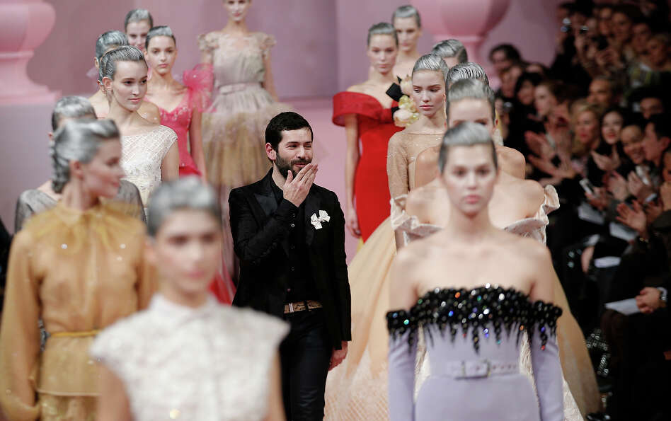 French fashion designer Alexis Mabille, centre, blows a kiss as he receives acknowledgement for his