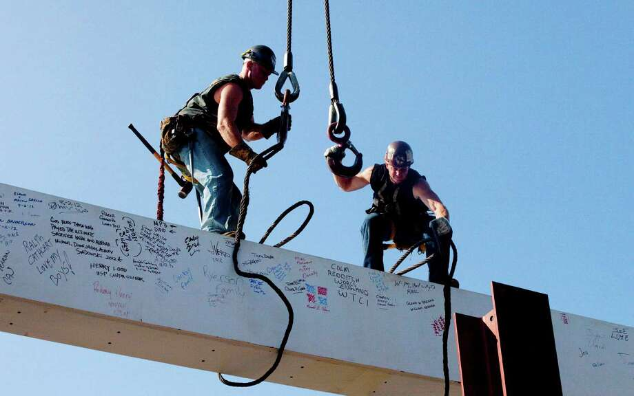 "FILE - In this file photo of Aug. 2, 2012, ironworkers James Brady, left, and Billy Geoghan release the cables from a steel beam after connecting it on the 104th floor of One World Trade Center in New York. The beam was signed by President Barack Obama with the notes: ""We remember,"" ''We rebuild"" and ""We come back stronger!"" during a ceremony at the construction site June 14. Also adorned with the autographs of workers and police officers at the site, the beam will be sealed into the structure of the tower, which is scheduled for completion in 2014. Photo: Mark Lennihan, AP / AP"