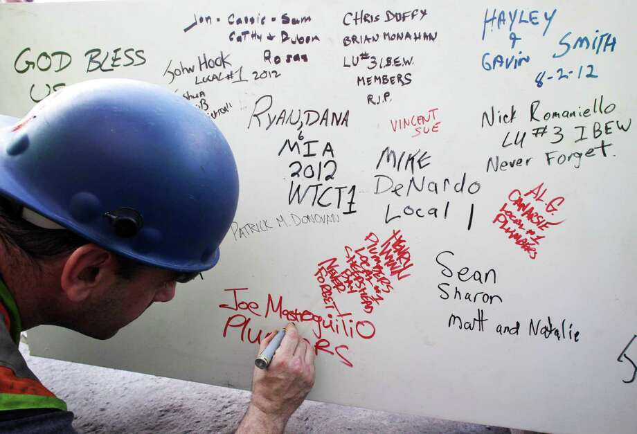 "FILE- In this Aug. 2, 2012 file photo, a construction worker signs a ceremonial steel beam at One World Trade Center in New York. The beam was signed by President Barack Obama with the notes: ""We remember,"" ''We rebuild"" and ""We come back stronger!"" during a ceremony at the construction site June 14. The beam, having since adorned with the autographs of workers and police officers at the site, will be sealed into the structure of the tower, which is scheduled for completion in 2014. Photo: Mark Lennihan, AP / AP"