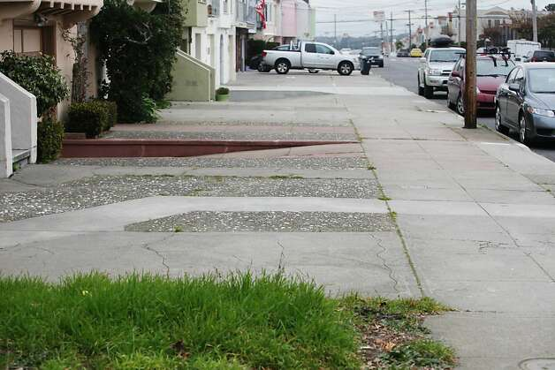 A front yard which hasn't been paved over is seen in the foreground and beyond it a row of paved over front yards are seen in front of homes in the Outer Sunset along 29th Avenue. Photo: Lea Suzuki, The Chronicle