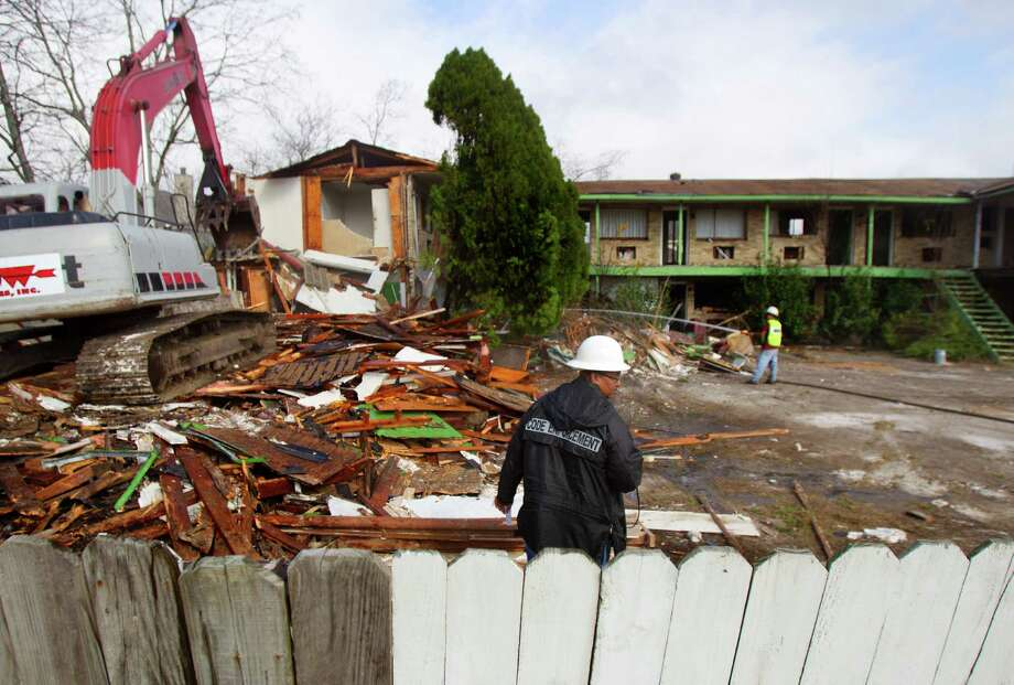A crew member with Arrow Services Inc., surveys the rubble as the demolition proceeds. Photo: Cody Duty, Houston Chronicle / © 2012 Houston Chronicle