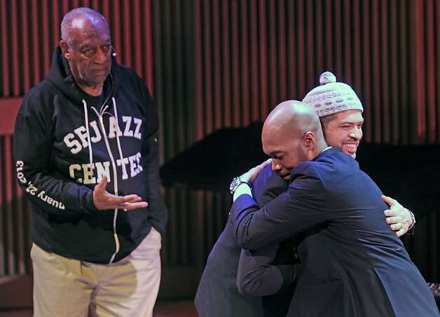 Master of ceremonies Bill Cosby (left) watches as Jason Moran (with hat) and drummer Eric Harland hug after their duet. Photo: Lance Iversen, The Chronicle