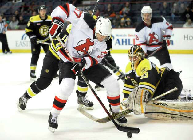 Devils' Chris McKelvie (37), center, works the puck as Bruins goalie Michael Hutchinson (33), right, guards the net during their hockey game on Saturday, Dec. 15, 2012, at Times Union Center in Albany, N.Y. (Cindy Schultz / Times Union archive) Photo: Cindy Schultz / 00020442A