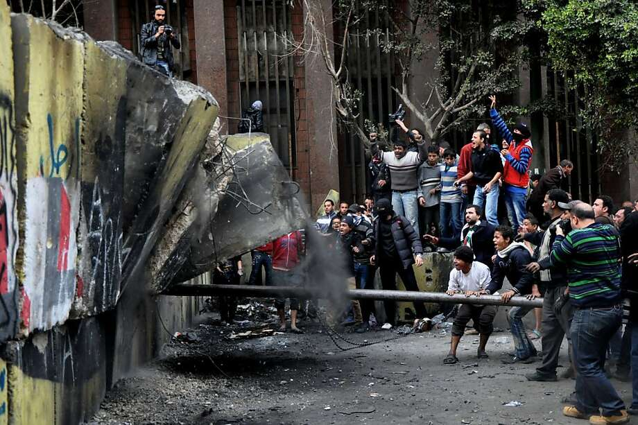 Mr. Morsi, tear down this wall! Protesters try to smash a cement wall built to prevent them from reaching parliament and the Cabinet building near Cairo's Tahrir Square. Egypt's black-clad riot police fired tear gas in fierce dawn clashes with dozens of protesters. Photo: Hussein Tallal, Associated Press