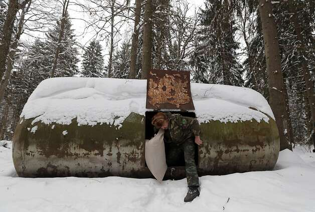 'Boulder' with a trap door: Belarusian huntsman Ivan Makarevich pulls a bag of grain out from his secret hideout (actually an old tank) in the Nalibokskaya Forest Reserve. He put out the grain for deer and other animals that are having trouble feeding themselves due to the cold weather and heavy snow. Photo: Sergei Grits, Associated Press