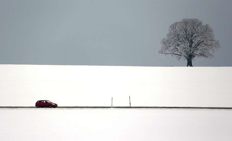 Bad weather: A car motors through a barren winter landscape near Bad Toelz, Germany. Photo: Matthias Schrader, Associated Press
