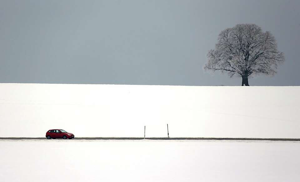 Bad weather: A car motors through a barren winter landscape near Bad Toelz, Germany.