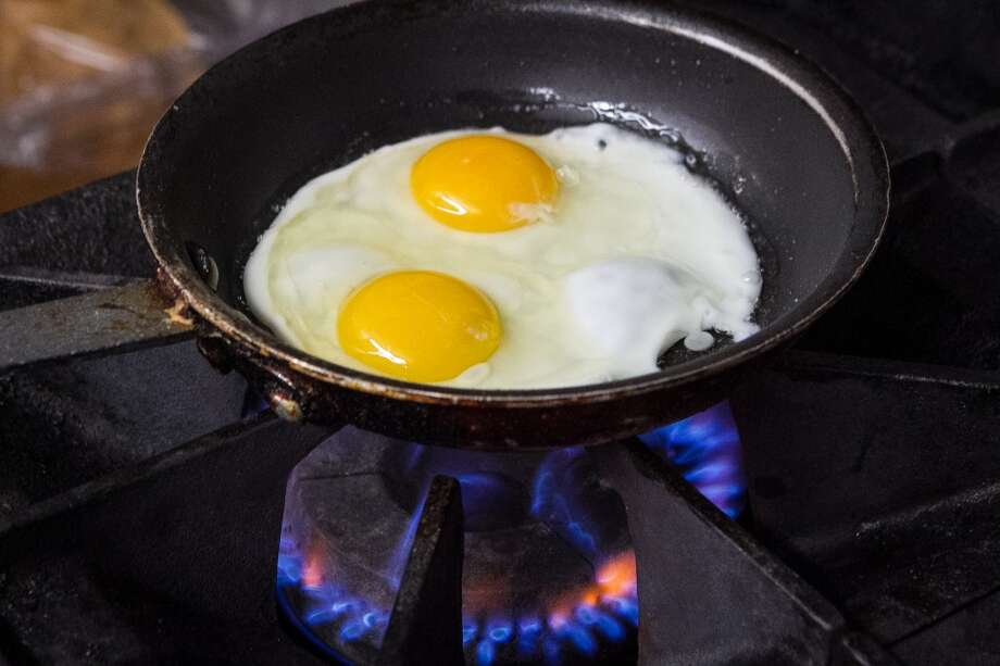 Eggs being fried for the Big Island plate at Grindz.