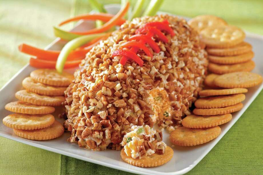 Kick off your Super Bowl party with this Cheesy Football appetizer that's shaped like a football: pimento strips make the lacing.