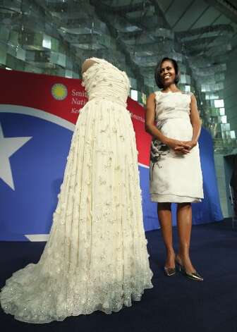 This March 9, 2010, file photo shows first lady Michelle Obama standing with the chiffon Jason Wu gown that she wore to the 2009 inaugural ball as she donates it to the Smithsonian's National Museum of American History in Washington.